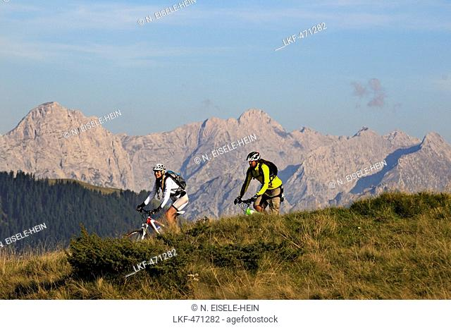 Mountain bikers passing Winklmoosalm, Berchtesgaden Alps in background, Chiemgau, Upper Bavaria, Germany
