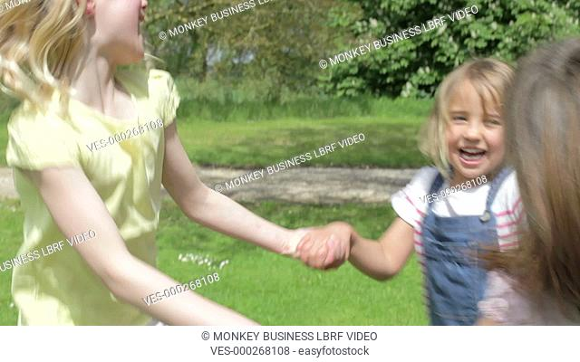 Three young girls hold hands and spin around until they all fall on grass.Shot on Canon 5D Mk2 at a frame rate of 25fps