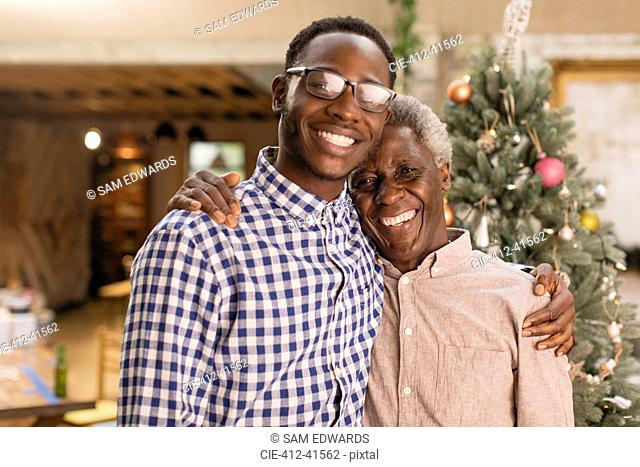 Portrait smiling grandfather and grandson hugging in front of Christmas tree