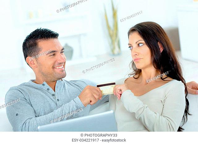 Playful couple about to spend money on-line