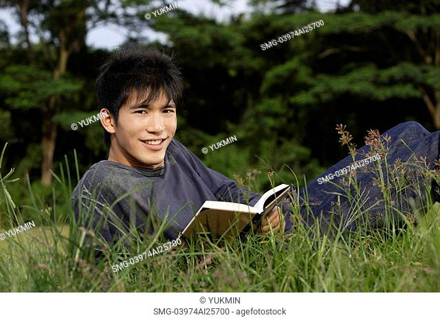 Young man reading in grass