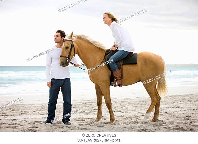 Man and woman with horse on the beach