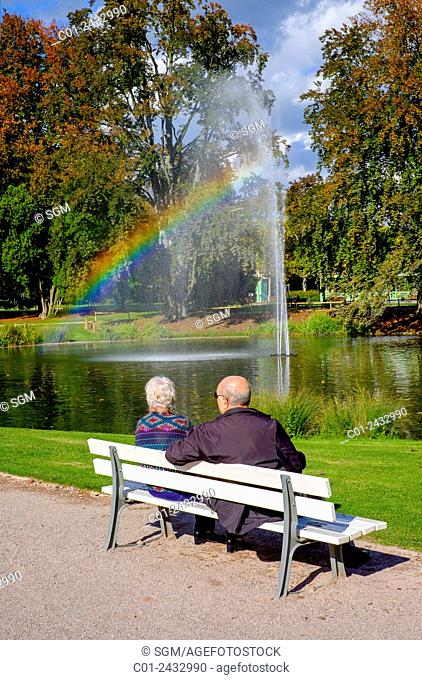 Elderly couple on bench and jet of water with rainbow Parc de l'Orangerie park Strasbourg Alsace France