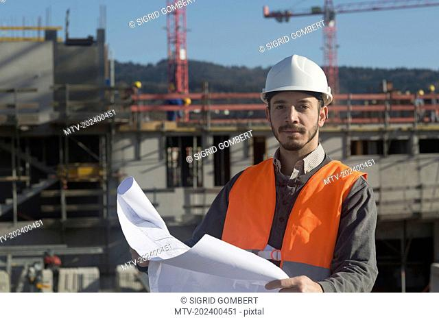 Portrait of a young male engineer holding blueprint at construction site, Freiburg Im Breisgau, Baden-Württemberg, Germany