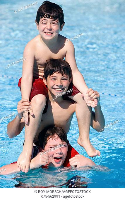 Three brothers piggyback in pool