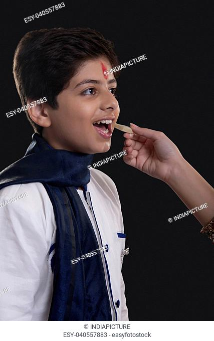 Close up shot of hand feeding sweets to her brother at Bhaidooj