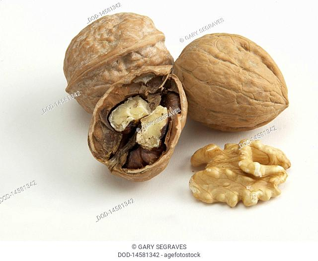 Walnuts and walnut shell against white background