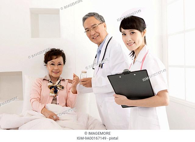 Doctor,nurse and senior smiling at the camera together