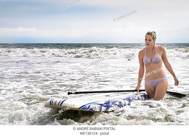 Young woman with paddle board walking through the surf. Riviera Nayarit, Pacific Coast, Mexico