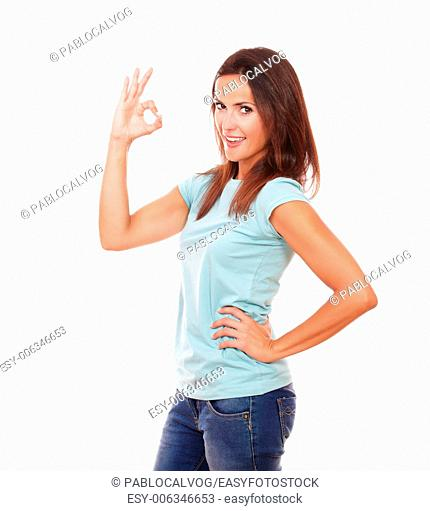 Portrait of adult hispanic woman on blue t-shirt with ok sign and funny face smiling at you while standing on isolated studio