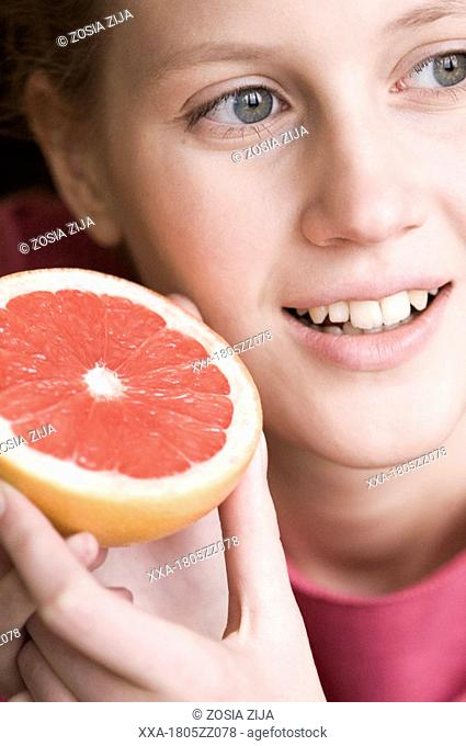 young woman with half of grapefruit