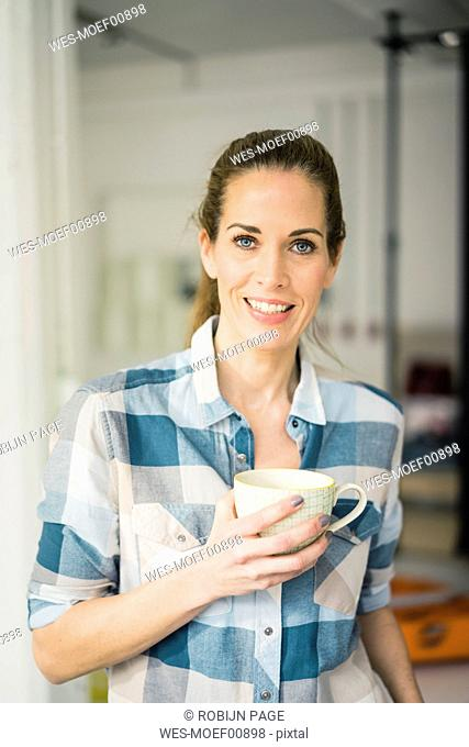 Portrait of a beautiful woman, drinking coffee at home