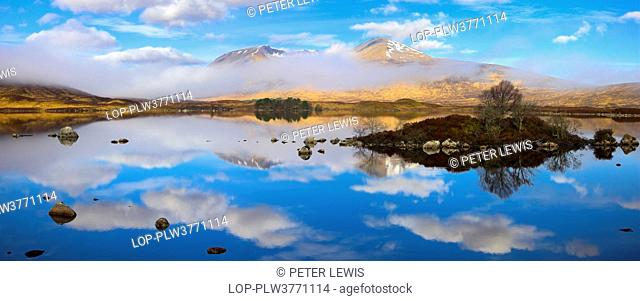 Scotland, Argyll and Bute, Rannoch Moor. A panoramic view of Lochan na h-Achlaise featuring a rare combination of clouds, mirror reflections