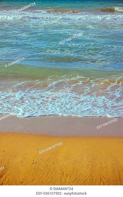 Soft foam wave of sea on sandy beach verticak as background