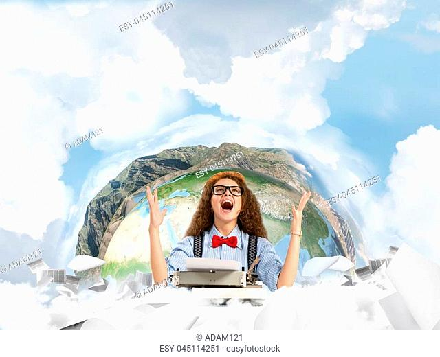 Happy and young woman writer in hat and eyeglasses looking happy while sitting with typing machine at the table with flying papers and Earth globe among cloudy...