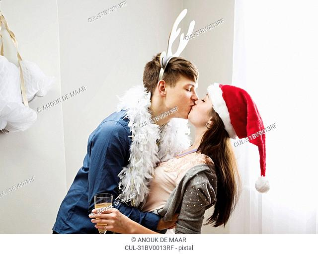 Couple kissing wearing christmashats