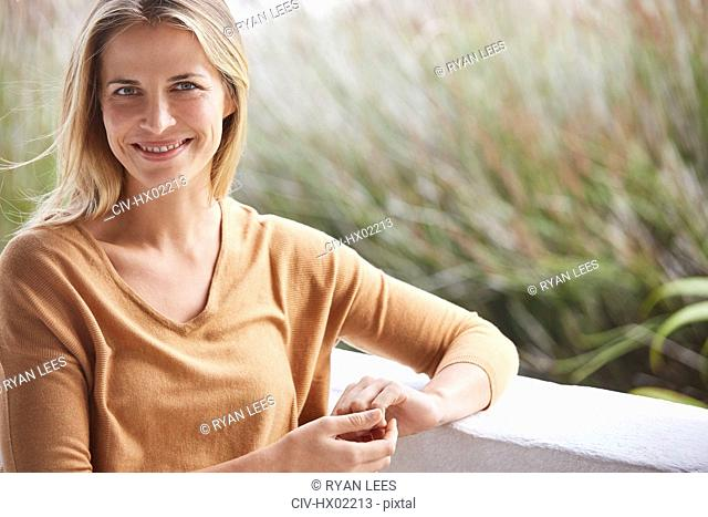 Portrait smiling blonde woman on patio