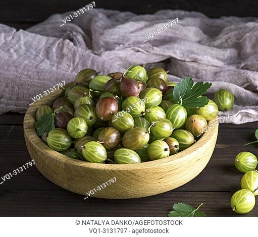 ripe green gooseberry in a wooden bowl on a table