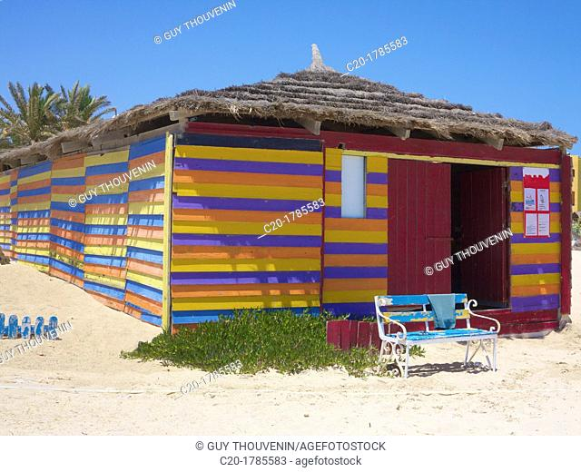 colored wooden beach hut on beach with old blue bench, Djerba, Tunisia