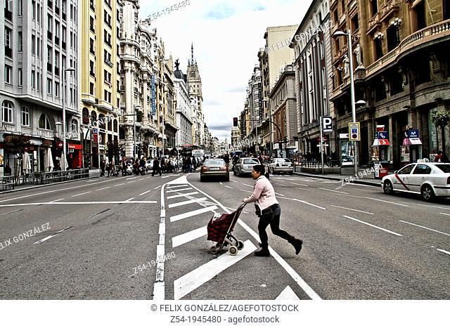 Pedestrian crossing the Gran Via street, Madrid, Spain