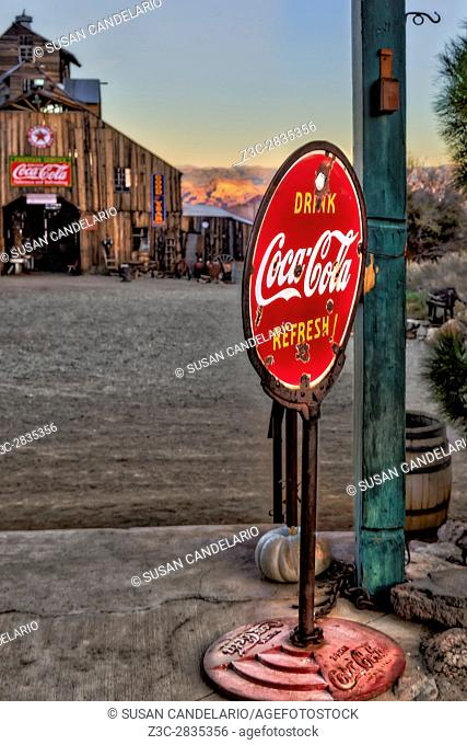 Drink Coca Cola Refresh - Vintage Coca Cola sign on rusted stand in the ghost town's general store. An Americana Barn is in the background along with the...