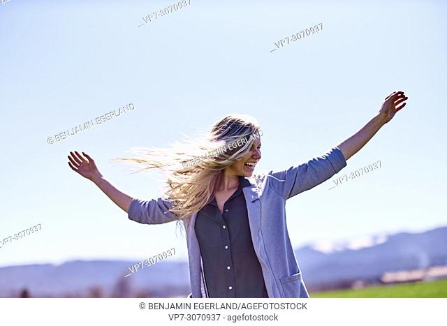 Vibrant woman shaking hair and enjoying sunny weather, against blue sky. Waakirchen, Bavaria, Germany