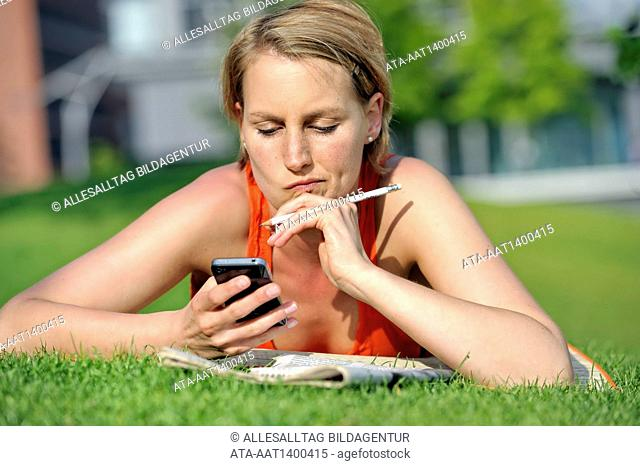 Woman lying in the grass looking at her iphone