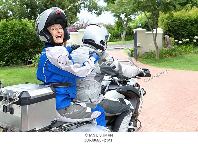 Portrait of laughing senior woman wearing helmet on back of motorcycle in driveway