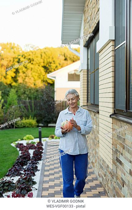 Smiling senior woman with harvested pumpkin in the garden
