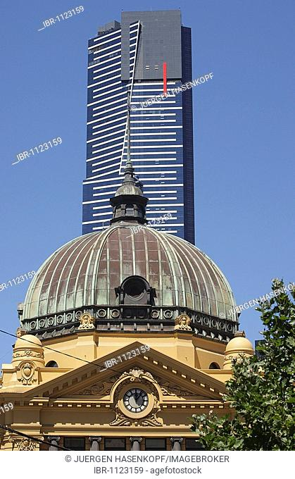 Eureka Tower skyscraper, residential building, in the front the historical victorian train station Flinders Street station, contrast new and old architecture