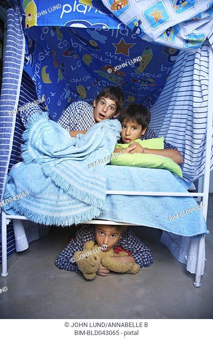 Hispanic boys hiding in bed fort