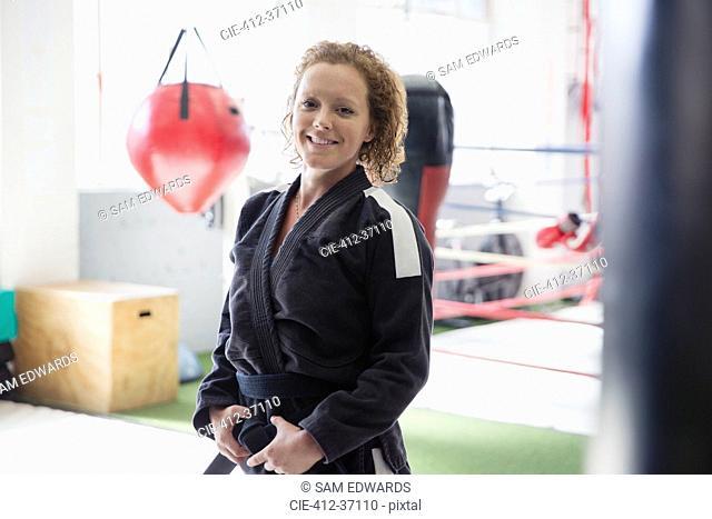 Portrait confident woman in judo uniform in gym