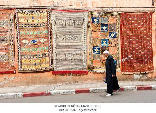 Man wearing a headdress, a traditional Djellabah, and slippers, Babouche, walking past a house wall with carpets hanging for sale, Marrakech, Morocco, Africa