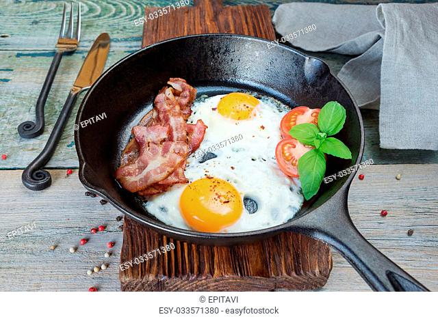 Fried eggs, strips of bacon, halved tomato and basil in a cast iron skillet on an old wooden table in rustic style