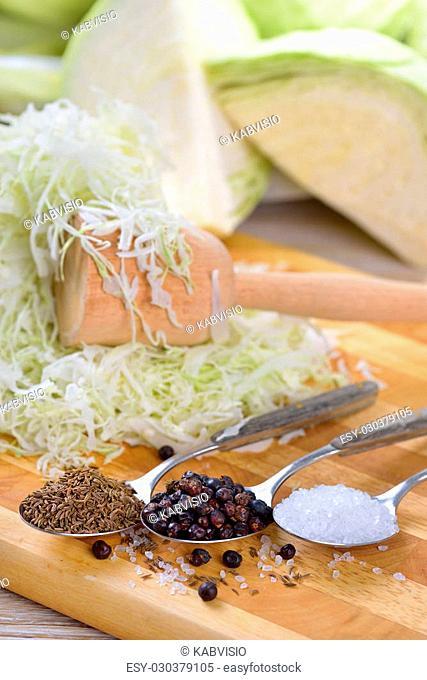 Food fermentation, preparation for making sauerkraut: Sliced white cabbage, caraway seeds, juniper berries, salt and a pounder
