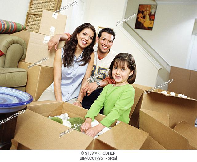 Family unpacking cardboard boxes in their new house