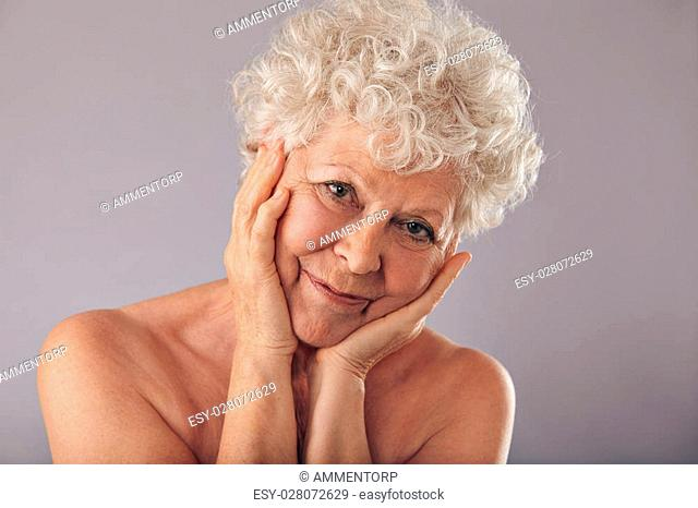 Close-up studio portrait of attractive senior woman with her head resting in her hands against grey background. Happy old woman with hands on face looking at...