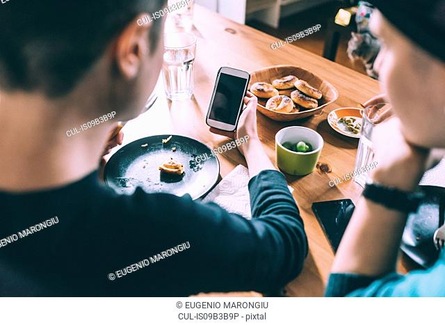 Over shoulder view of two young female friends reading smartphone texts at kitchen table
