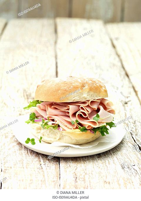 Wafer thin smoked ham in bread roll with leafy vegetables
