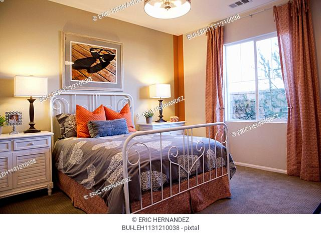 Cozy and tidy bed in contemporary bedroom with lit table lamps