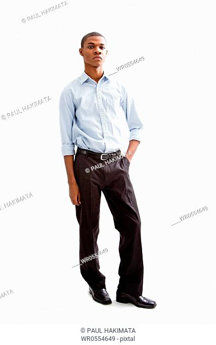 Young African business man standing relaxed and secure with hands in pocket, isolated