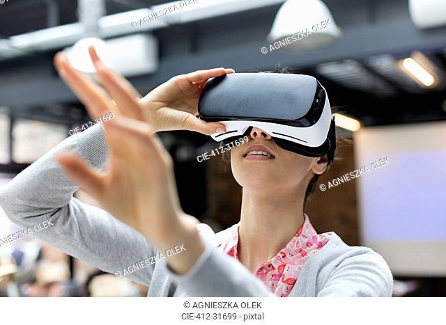Woman trying virtual reality simulator glasses glasses reaching