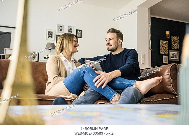 Smiling couple sitting on couch at home with tablet