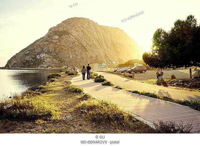 Tourist couple strolling toward Morro Bay Rock, Morro Bay, California, USA