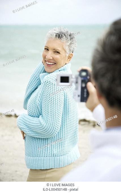 A senior man filming his partner on a video camera