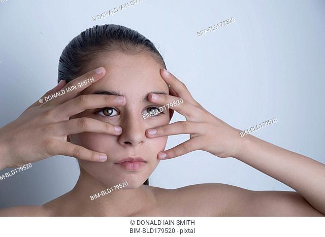 Mixed race girl touching her face