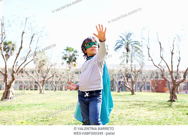 Little boy dressed up as a superhero posing on a meadow