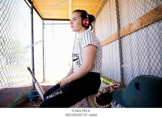 Pensive middle school girl softball player listening to music with headphones in dugout