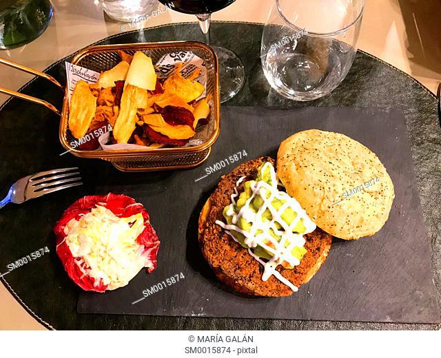 Vegetarian hamburger with salad, guacamole and vegetarian chips
