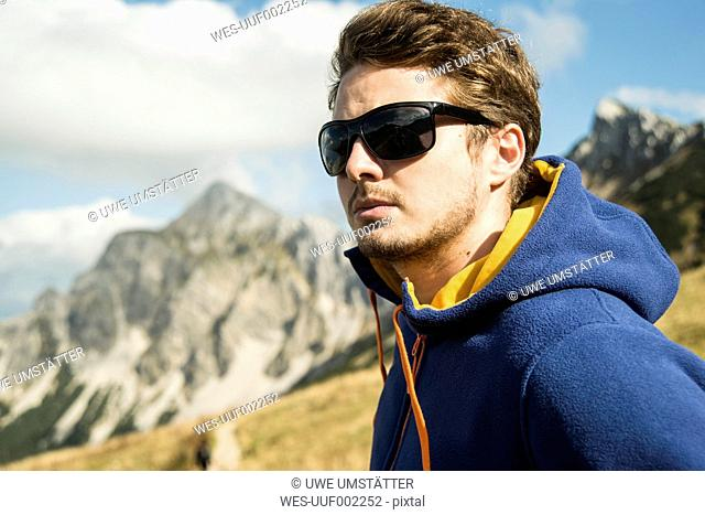 Austria, Tyrol, Tannheimer Tal, young man wearing sunglasses
